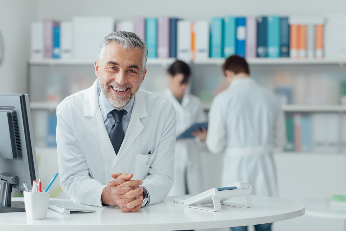 Physician in white lab coat behind front desk ready to consult patients